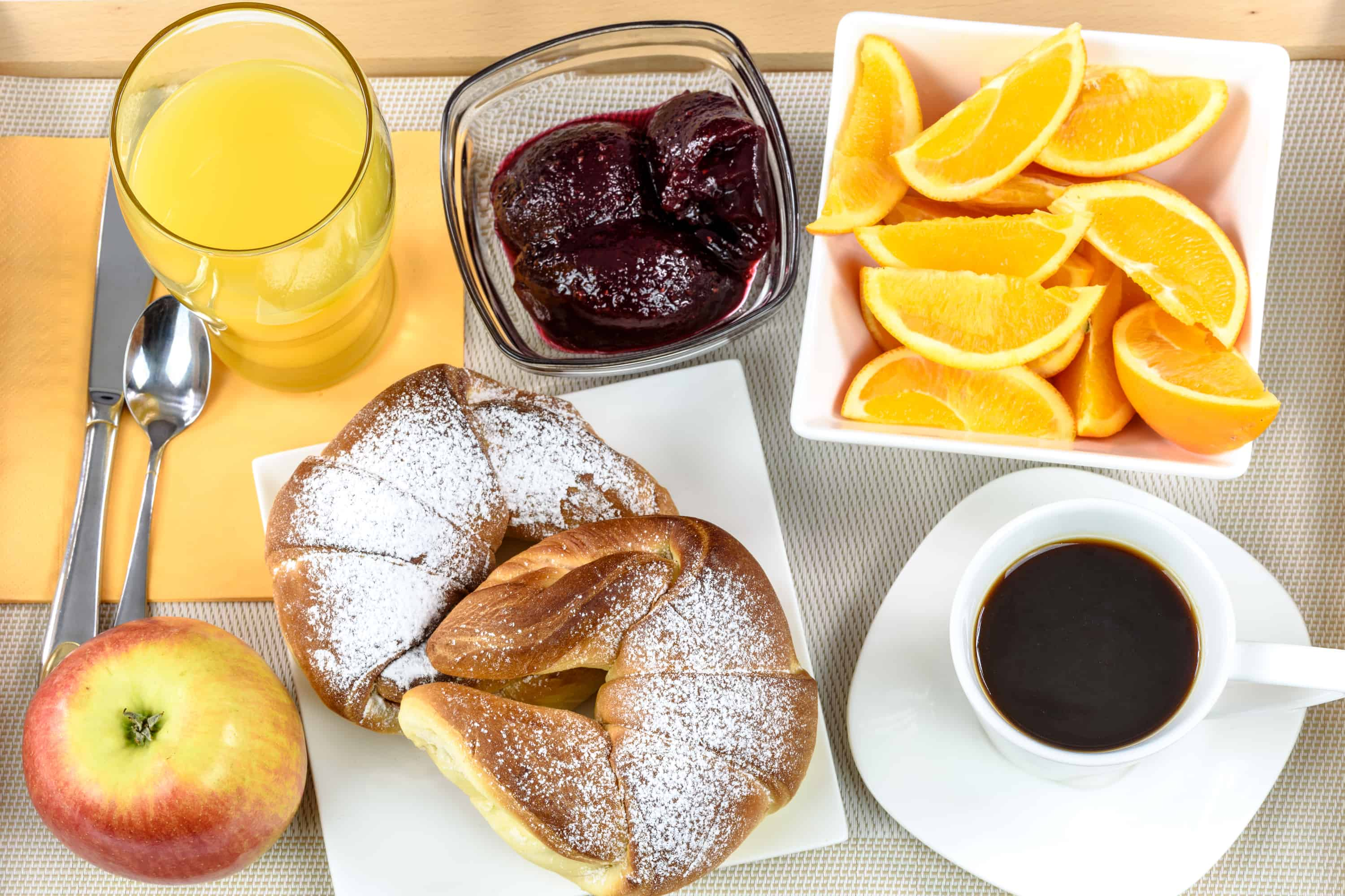 Overhead shot on hotel's breakfast tray with croissants, coffee, oranges, juice, jam, apple and cutlery